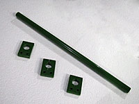 Three small green painted parts and a rod.